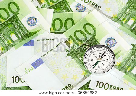 euro bank notes and a compass