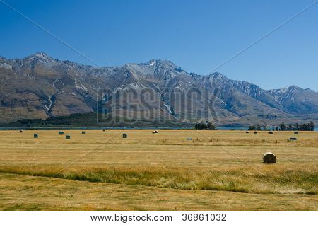 Straw Haystacks On The Field After Harvest, With A Lake And Mountains At The Background