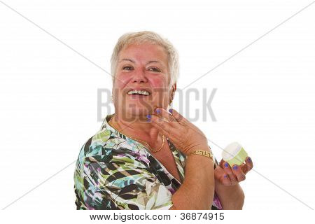 Senior Woman Applying Lotion On Her Face