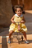 stock photo of centenarian  - Happy girl riding a centenarian toy tricycle - JPG