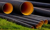 stock photo of mixing faucet  - mix of concrete pipes black cover with orange inside - JPG