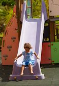 stock photo of chute  - Small Hispanic girl sliding down a chute - JPG