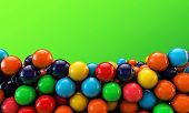 picture of gumballs  - many colored gumballs isolated on green background - JPG
