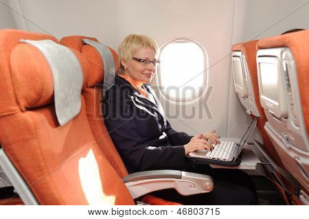 smiling businesswoman posing with laptop on the board of plane in ecomomy class of aeroflot