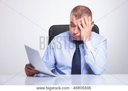 senior business man disappointed by what he reads from some documents, at his office. on gray background