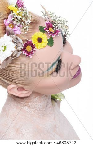 closeup of a young beauty woman wearing a wreath of flowers and an excentric make up while looking away from the camera. on white background