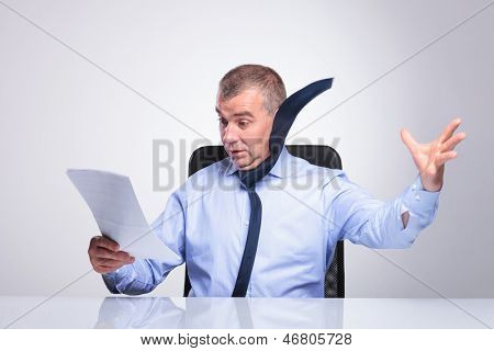 senior business man at the desk is blown of by what he reads from some documents, with his tie flying. on gray background