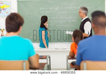 high school girl been called to chalkboard by senior teacher during biology lesson