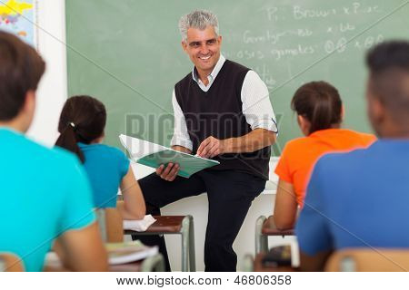 smiling senior teacher teaching group of high school students in classroom