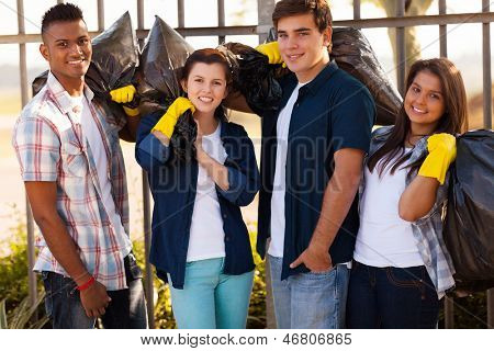 group of smiling teenage volunteers with garbage bags after cleaning the streets