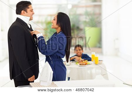 caring indian woman helping her husband with his tie before going to work