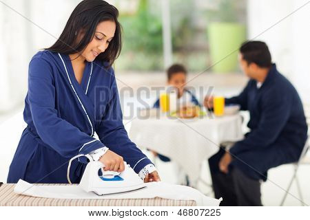 beautiful housewife ironing clothes for the family in the morning