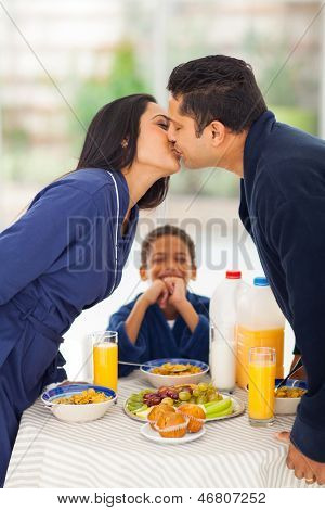 little boy is laughing when seeing his parents kissing before breakfast