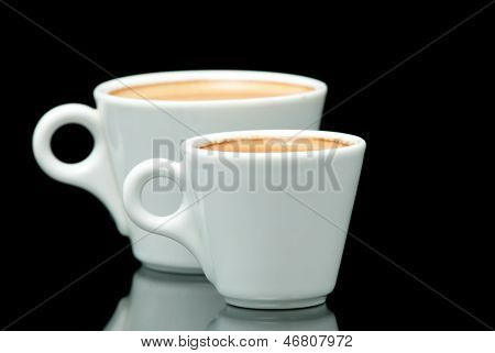 two white coffe cups on the black background