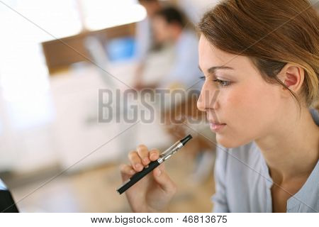 Portrait of woman smoking with electronic cigarette