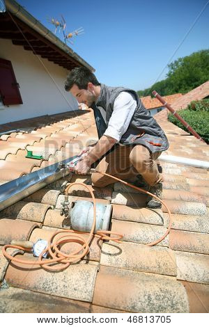 Roofer working on house roof to fix gutter