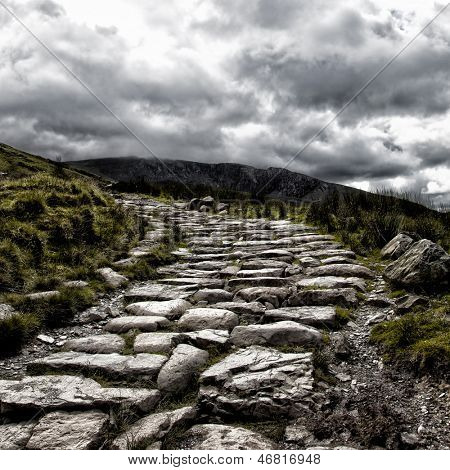Dramatic depiction of the dry stone hikers path leading to the summit of Mount Snowdon, under a stormy sky, Snowdonia, North Wales.