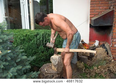 Strong Man Is Chopping Wood With An Axe And Hummer. Renewable Resource Of Energy.