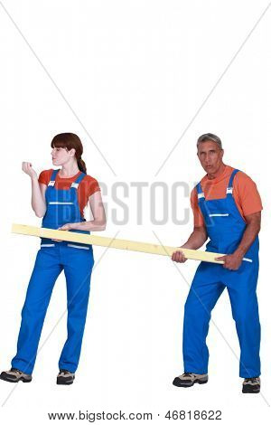 Construction couple carrying timber
