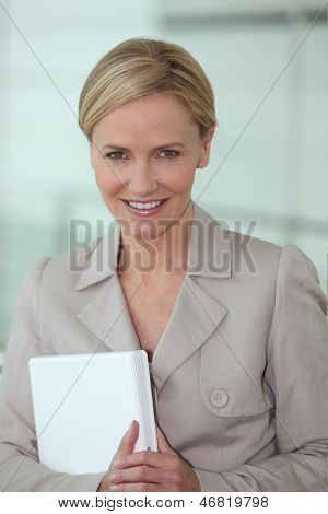 Blond executive holding laptop computer