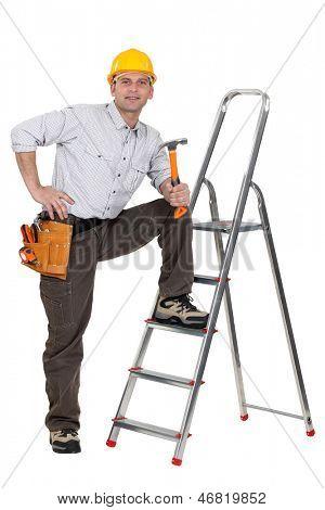 carpenter with leg resting on ladder holding hammer