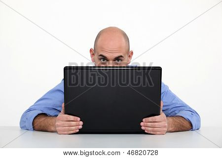 Man hiding behind laptop