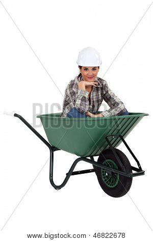 Tradeswoman sitting in a wheelbarrow