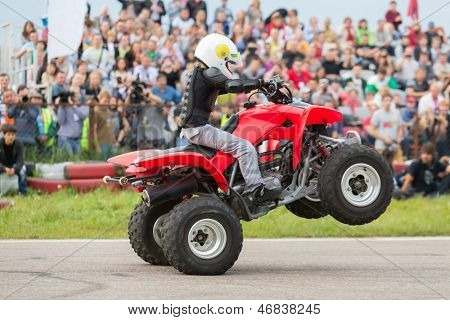 MOSCOW - AUG 25: Kid rides on the rear wheels on a quad bike on Festival of art and film stunt Prometheus in Tushino on August 25, 2012 in Moscow, Russia. The festival was organized in 1998.