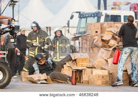 MOSCOW - AUG 25: Rescue workers help person after jumping from height into burning box on Festival of art, film stunt Prometheus in Tushino, Aug 25 2012, Moscow Russia. Festival was organized in 1998.