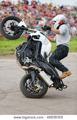 MOSCOW - AUG 25: Biker rides on the rear wheel on Festival of art and film stunt Prometheus in Tushino on August 25, 2012 in Moscow, Russia. The festival was organized in 1998.