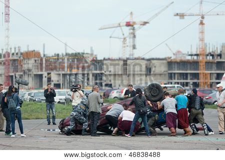 MOSCOW - AUG 25: Rescuers rushed to the overturned car on Festival of art and film stunt Prometheus in Tushino on August 25, 2012 in Moscow, Russia. The festival was organized in 1998.