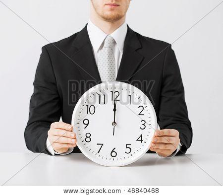 close up of man holding wall clock