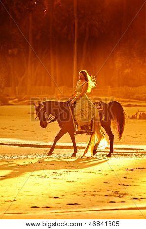 mujer vestido medieval montando a caballo en la playa al atardecer