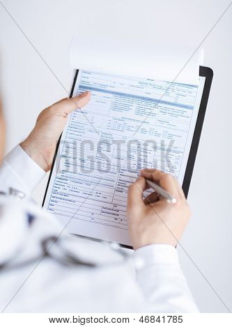 close up of male doctor holding prescription paper in hand