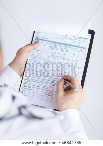 close-up de médico homem, segurando na mão o papel de prescrição