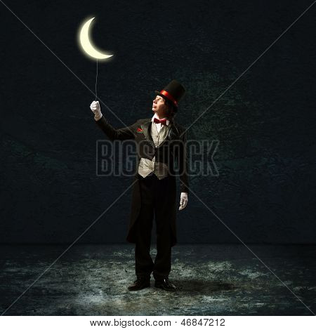 magician keeps the moon on a string