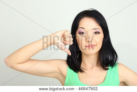 Young woman showing thumbs down on grey background
