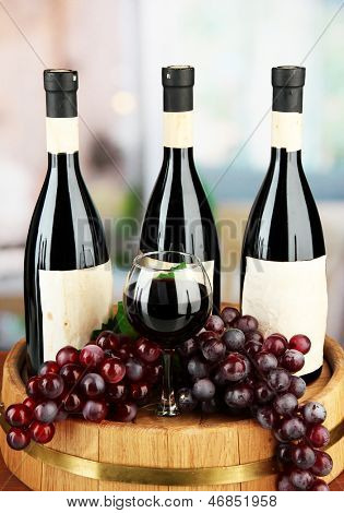 Composition of wine bottles, glass and  grape,on wooden barrel, on bright background