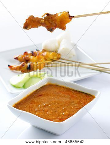 Chicken satay, grilled and skewered meat, served with peanut sauce, cucumber and ketupat. Traditional Malay food. Delicious hot and spicy Malaysian dish, Asian cuisine.