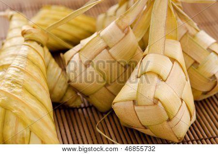 Ketupat or packed rice dumpling. Delicious traditional Malay ramadan food. Popular Malaysian food on bamboo mat.