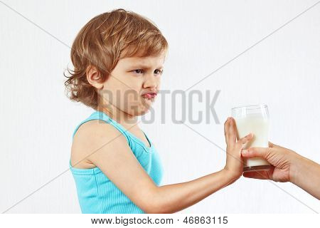 Little cute blonde boy refuses drink fresh milk