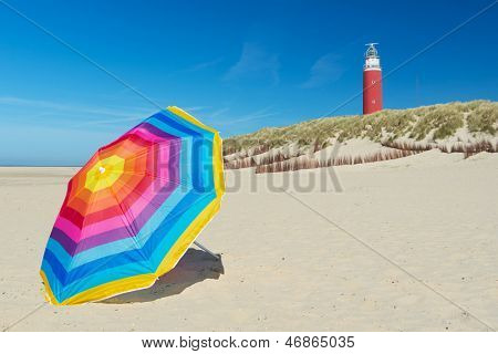 lighthouse and colorful parasol on Dutch wadden island Texel