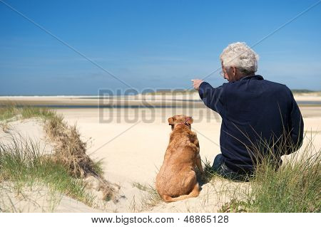 Man sitting with dog on sand dune at Dutch beach on wadden island Texel
