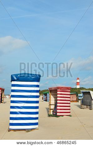 Beach of German wadden island with typical striped chairs and lighthouse