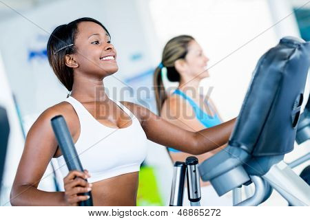 Fit women exercising at the gym on an x-trainer