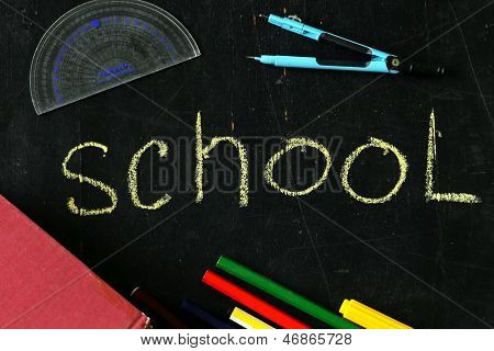 stationery (pen, pencil, ruler, compass) and a book on black school board background