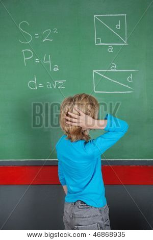 Rear view of confused little boy looking at board in classroom