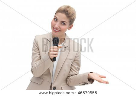 Amazed businesswoman speaking on microphone at public presentation