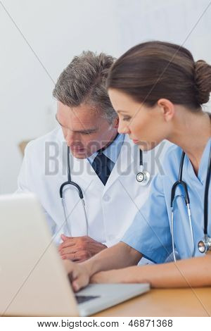 Two doctors working on a folded while using a laptop