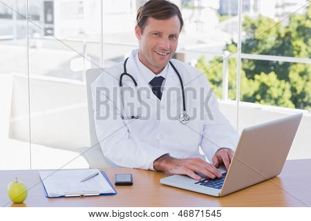 Smiling doctor working on a laptop on his desk